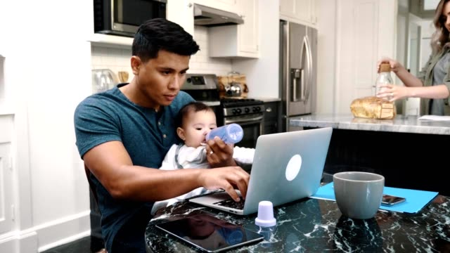 Busy dad feed his baby girl while using laptop Mid adult dad works from home while feeding his baby girl a bottle. His wife is preparing breakfast in the background. latin american and hispanic ethnicity stock videos & royalty-free footage