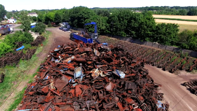 Busy day at junkyard. Mechanical claw drop metal scrap. Aerial view