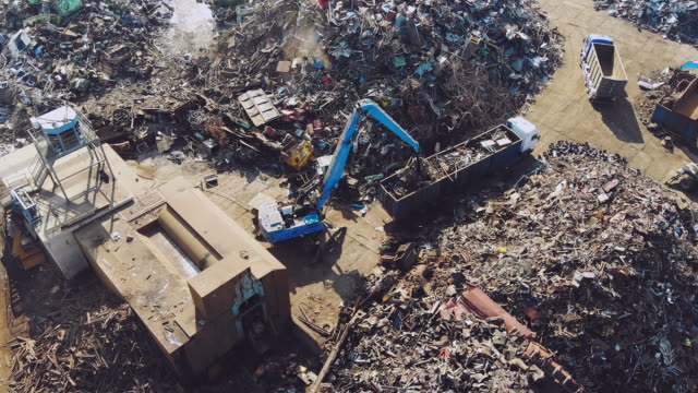 Busy day at junkyard. Mechanical claw drops metal scrap. Aerial view
