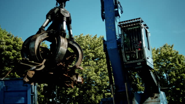 Busy day at junkyard. Mechanical claw drops metal scrap