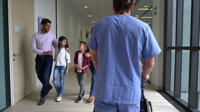 Busy day at the hospital, patients and healthcare staff walking through the corridor Busy day at the hospital, patients and healthcare staff walking through the corridor - Healthcare concepts entrance stock videos & royalty-free footage