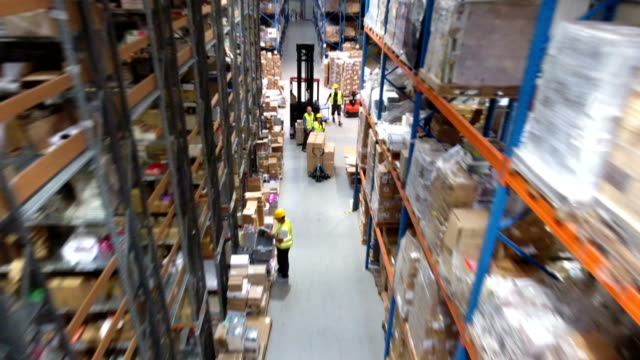 vídeos de stock e filmes b-roll de busy day at warehouse. worker driving on a forklift. drone point of view - packaging