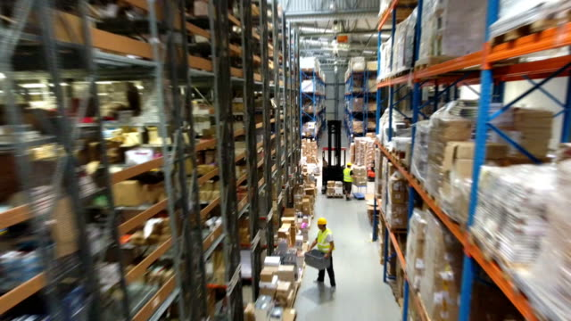 Busy day in the warehouse. Drone point of view Man in the warehouse driving on a forklift. Picking up cardboard boxes forklift stock videos & royalty-free footage