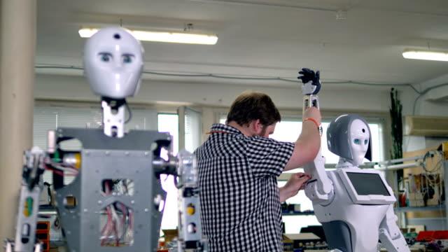vidéos et rushes de un ingénieur occupé assemble un des deux robots. - membre partie du corps