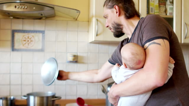 a busy father. a man with a child in the kitchen prepares lunch and feeds the baby from the bottle. father's day - samotny ojciec filmów i materiałów b-roll