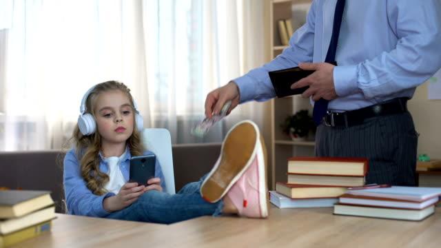 upptagen far ger fickpengar till lite nyckfull dotter med hörlurar - stavning bildbanksvideor och videomaterial från bakom kulisserna