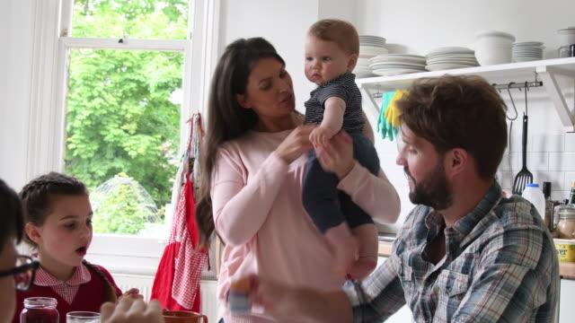 vídeos y material grabado en eventos de stock de familia feliz ocupada desayunando junto con bebé de tenencia de la madre - liado