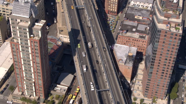 AERIAL: Busy highway sorrounded by condominium appartment buildings in New York AERIAL: Busy multiple lane highway running through Brooklyn, surrounded by residential condominium appartment buildings and blocks of flats. Manhattan bridge freeway through New York City on sunny day manhattan bridge stock videos & royalty-free footage