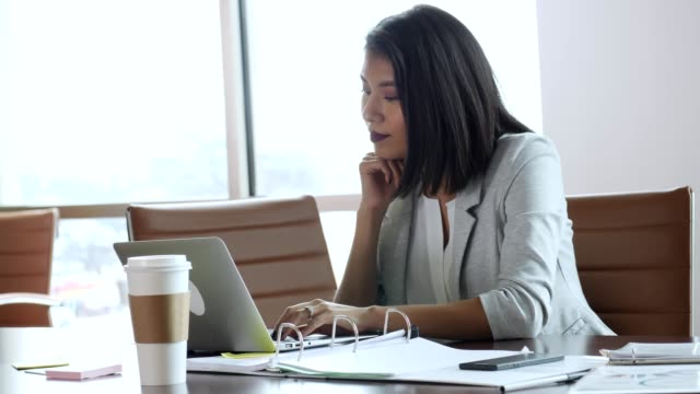 Busy Hispanic businesswoman works to meet deadline Confident businesswoman types quickly on laptop while in the office conference room. She rests her hand on her chin while looking at the laptop. e mail stock videos & royalty-free footage