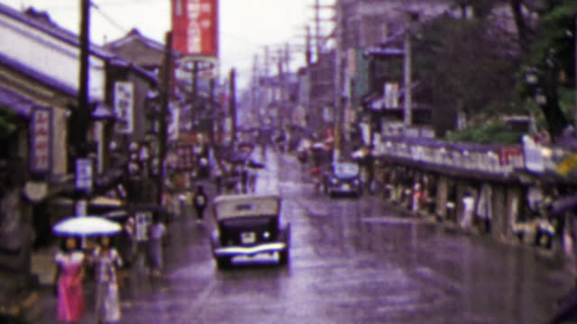 1951: Busy Japanese commercial street raining umbrellas drawn. video