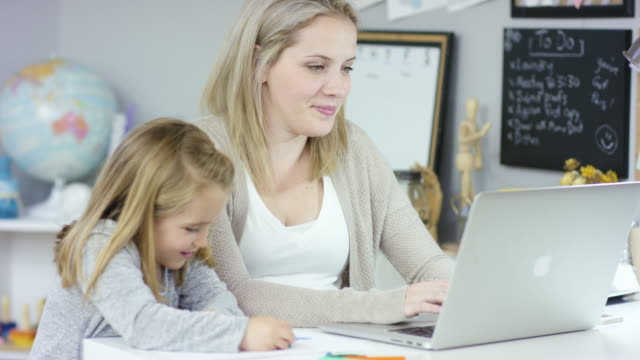 Busy Life A young caucasian mother is working on her laptop while her elementary age daughter is sitting beside her and drawing with crayons. life balance stock videos & royalty-free footage