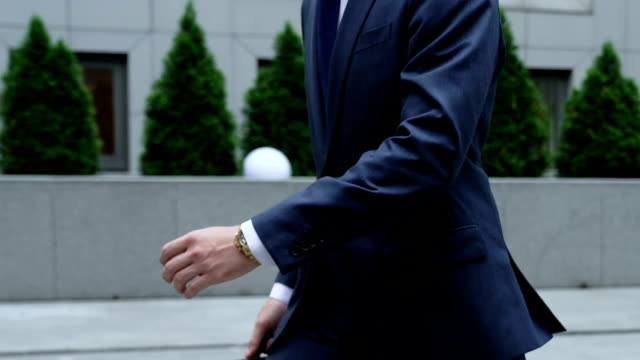 Busy man checks time in watches, hurries to office center, colleague outruns him