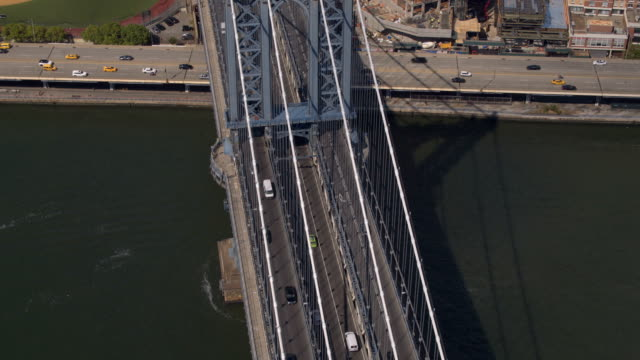 AERIAL: Busy Manhattan bridge highway running over East river into New York City AERIAL CLOSE UP: Manhattan bridge highway running from Brooklyn borough into downtown New York City. Flying above famous multiple lane Manhattan bridge with cars and semi trucks driving along in USA. manhattan bridge stock videos & royalty-free footage