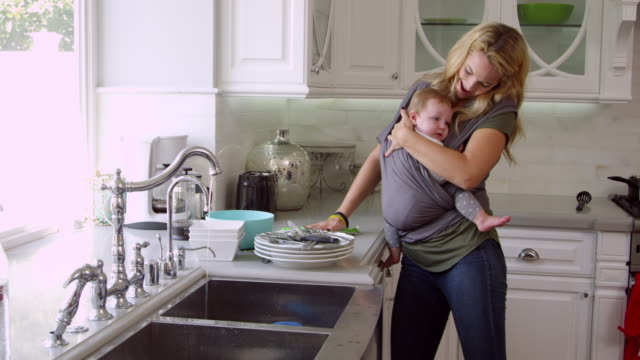 Busy Mother With Baby In Sling At Home Shot On R3D Busy Mother With Baby In Sling At Home Shot On R3D chores stock videos & royalty-free footage