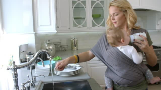 vídeos y material grabado en eventos de stock de madre ocupada con el bebé en honda en el hogar - liado