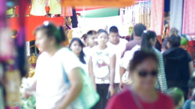 Busy Outdoor market with crowds of people walking soft focus video