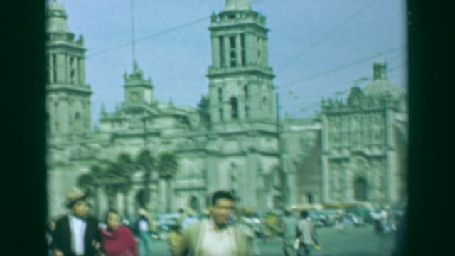 1952: Busy public square religious cathedral towers open outdoor downtown.