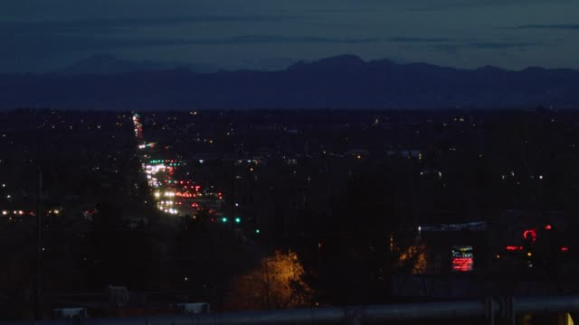 a busy road/highway in denver at night illuminated by headlights and tail lights with the rocky mountains in the background - ultra high definition television filmów i materiałów b-roll
