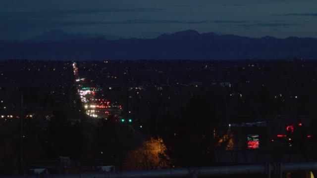 en upptagen väg/motorväg i denver på natten upplyst av strålkastare och bak ljus med rocky mountains i bakgrunden - ultra high definition television bildbanksvideor och videomaterial från bakom kulisserna