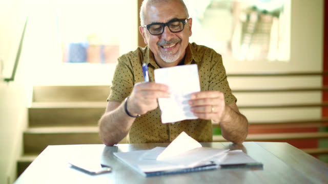 Busy senior man working with mail correspondence: responding the phone call, writing, opening the envelop, reading the letter. video