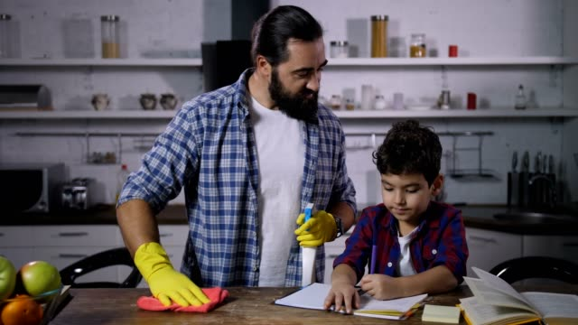 busy single dad cleaning house while son studying - padre single video stock e b–roll