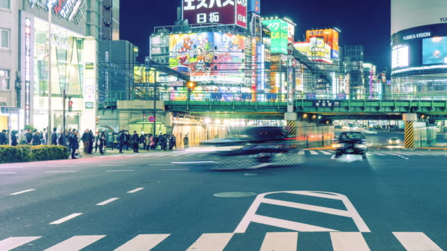 T/L MS Busy Traffic in Shinjuku at Night / Tokyo, Japan, panning to right