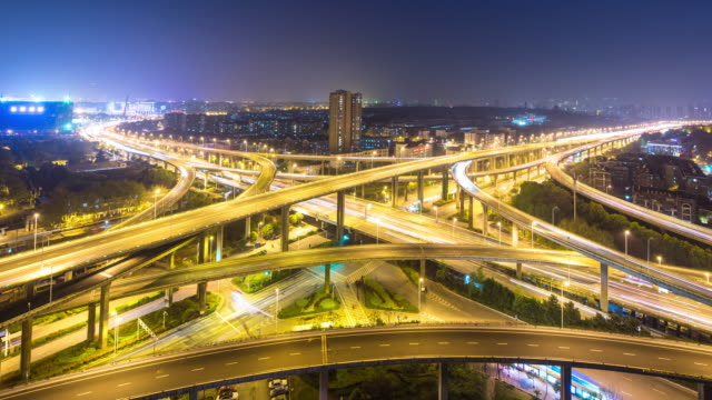 busy traffic on road junction with cityscape and skyline of hangzhou binjiang district at night timelapse 4k video