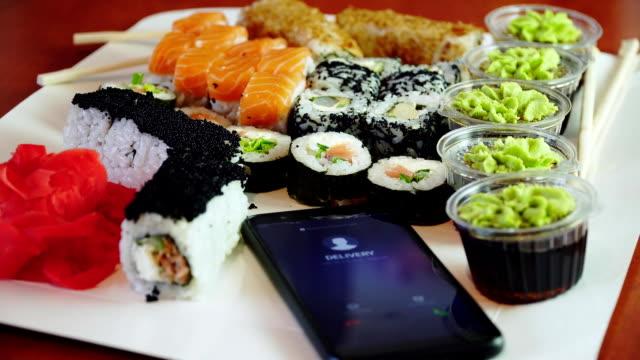 Upptagen kvinna operatör minskat samtal på mobil telefon medan packning sushi rullar i kartong för att skicka ordning video
