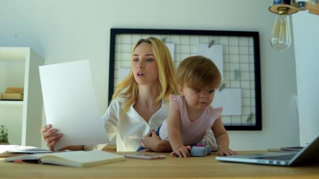 upptagen kvinna som arbetar med dokument hemma - working from home bildbanksvideor och videomaterial från bakom kulisserna