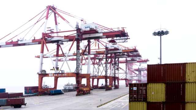 busy working crane loading containers from truck in harbor,timelapse. video