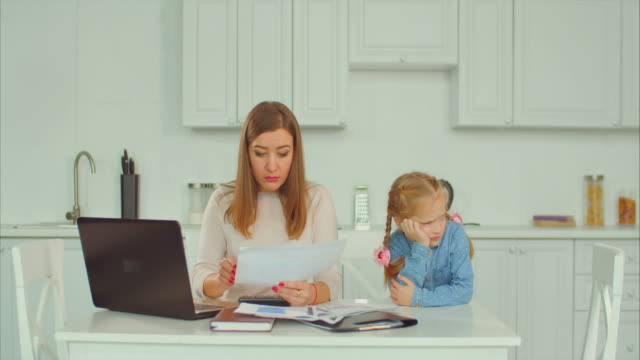 Busy working mother doesn't have time for her kid Irritated businesswoman busy working with laptop pc and paper documents ignoring her sad upset elementary age daughter in domestic kitchen. Anxious freelance mother left her child without attention. ignoring stock videos & royalty-free footage