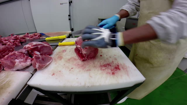 Butcher Cutting Raw Meat With Cleaver in Slaughterhouse video