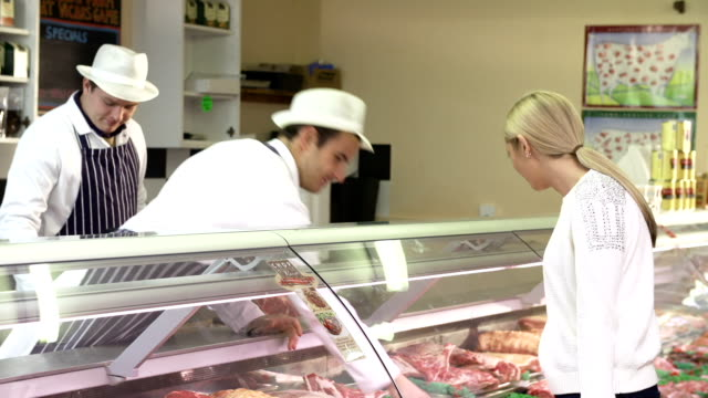 Butchers Serving Customers In Shop Woman asks butcher about selection of meat on display before selecting her purchase.Shot on Sony FS700 in PAL format at a frame rate of 25fps bank counter stock videos & royalty-free footage