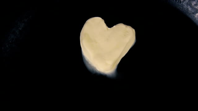 Butter in shape of heart melting on hot pan - Close up top view video