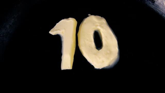 butter in shape of number ten melting on hot pan - close up top view - 10 11 лет стоковые видео и кадры b-roll
