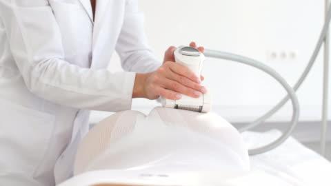 vídeos y material grabado en eventos de stock de zona de glúteos de la paciente femenina en traje blanco sometido a procedimiento de belleza masaje glp - parte del cuerpo humano