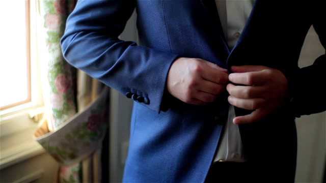 Buttoning a jacket hands close up. Stylish no face man in suit fastens buttons and straightens his jacket preparing to go out. Nervous fingers get ready before date or meeting fashion style weight fit video