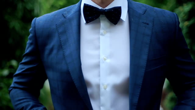 Buttoning a Jacket. Stylish Man in a Suit Fastening Buttons on His Jacket Preparing to Go Out Close up video