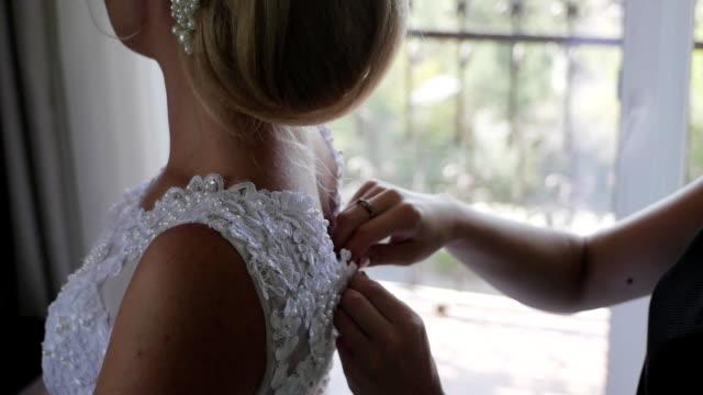Buttoning bride's wedding dress. Close up video