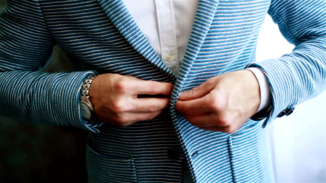 Buttoning jacket casual hands close up. Stylish well-dressed man arrange dressing in informal suit outfit preparing to go out. Expensive watch accessory. Macho luxury lifestyle golden youth style video