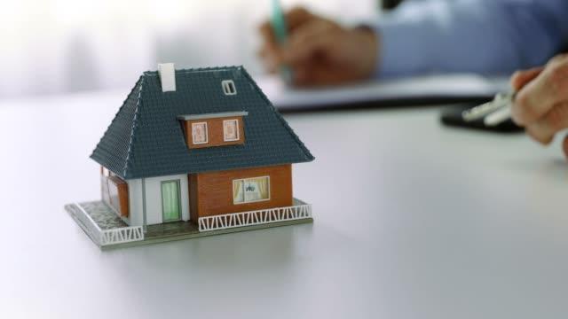 新しい家のコンセプトを買う-不動産エージェントは、オフィスで文書を書く - テーブル点の映像素材/bロール