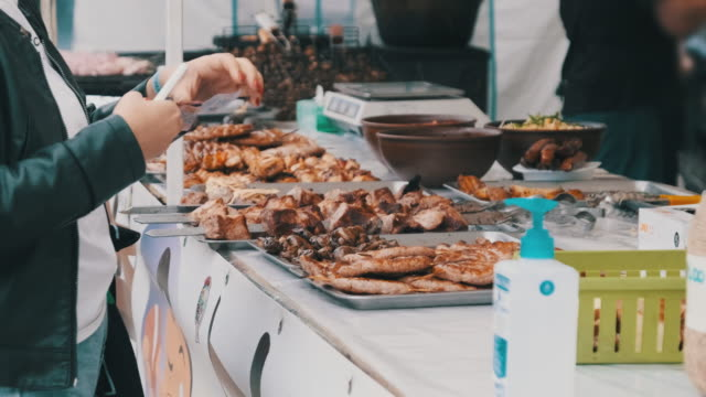 Buyer Buys Grilled Food and Transfers Money to the Seller at a Street Festival