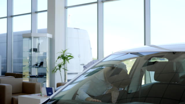 buyer car shows thumbs up, Auto business, car sale, technology and people concept - happy male client in auto show or salon video