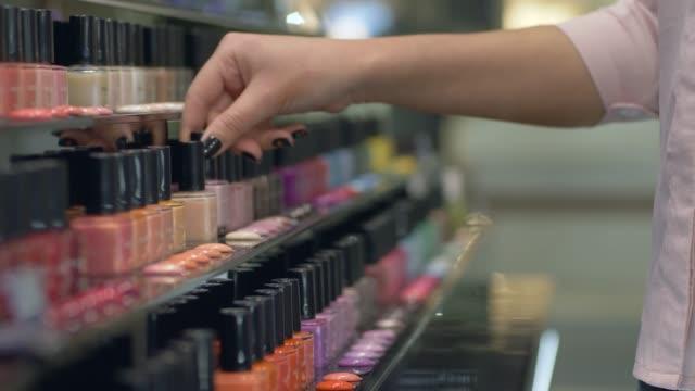 käufer mädchen wählt nagellack für maniküre und pediküre von großen anzahl von flaschen nagellack shop-schaukasten - kosmetische behandlung stock-videos und b-roll-filmmaterial