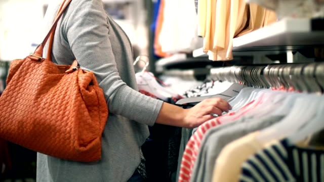 Buying clothes at retail store. Closeup side view of adult woman choosing clothes at department store. She's going through long clothes rack until she finds a piece of clothes she likes. She's carrying orange purse and wearing gray shirt. department store stock videos & royalty-free footage