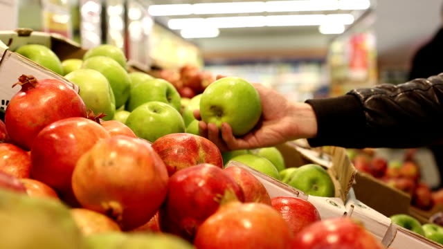 Buying green apples at the store