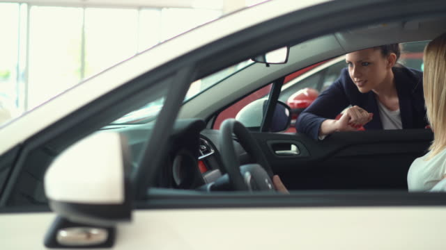 Buying new car. Closeup side view of mid adult couple sitting in a brand new car at a local dealership. Saleswoman is leaning through passenger window and explaining some features of the car. Dolly shot, stabilized camera. car salesperson stock videos & royalty-free footage
