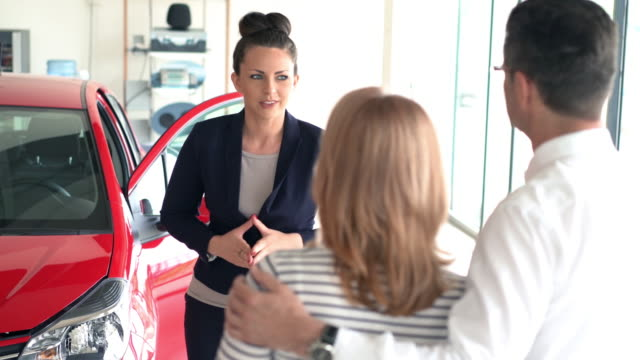 Buying new car. Closeup side view of mid adult couple sitting in front of a brand new car at a local dealership. Saleswoman is  explaining some features of the car. Dolly shot, stabilized camera. car salesperson stock videos & royalty-free footage