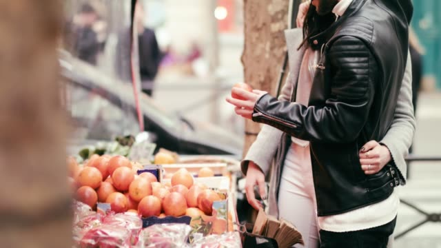 buying oranges at outdoor market - mercato frutta donna video stock e b–roll