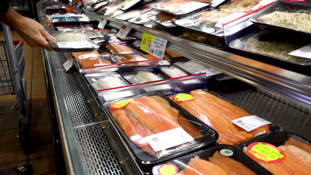 vídeos de stock e filmes b-roll de buying pre-packaged fish at the supermarket. - packaging